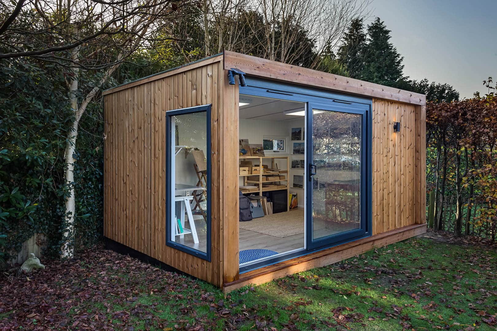 Inspiration redwood clad garden room with graphite sliding doors leading into space being used as an art studio