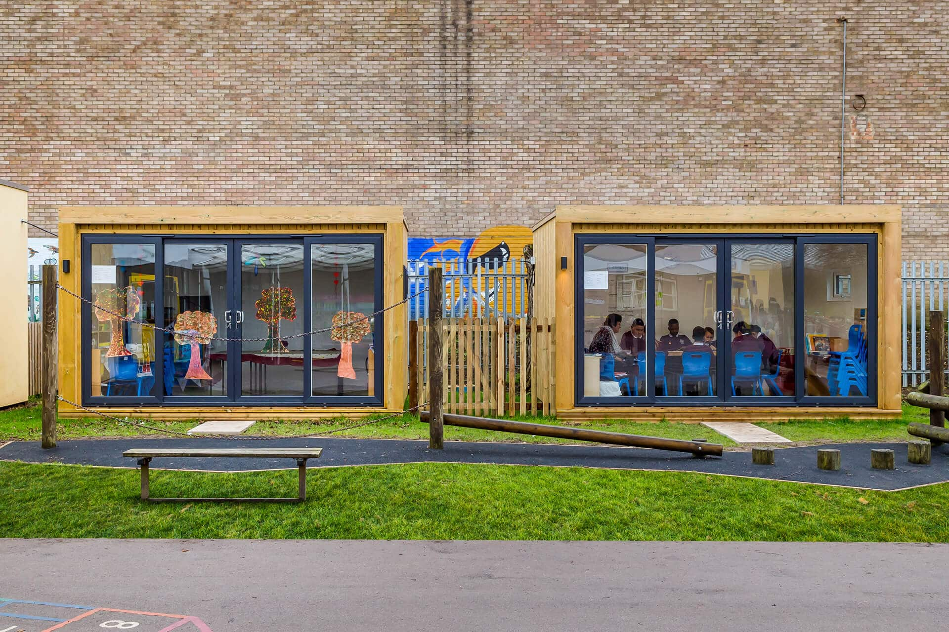 Two outdoor classroom garden rooms with small group of children sat on blue chairs in right building. Playground equipment in the foreground.