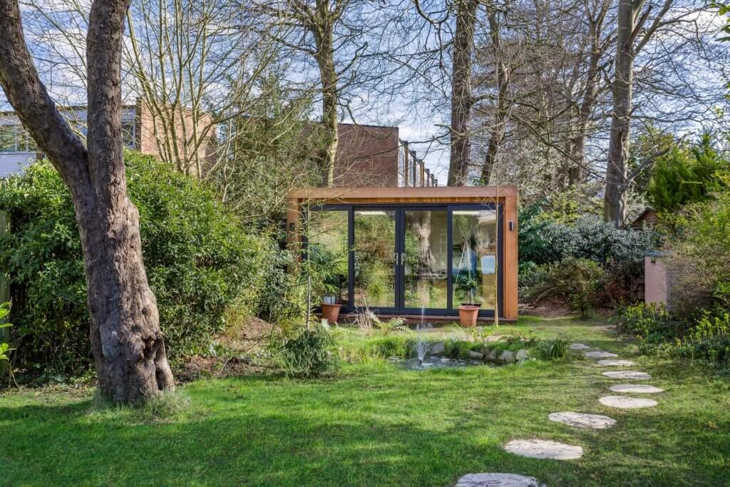 wooded garden with garden room