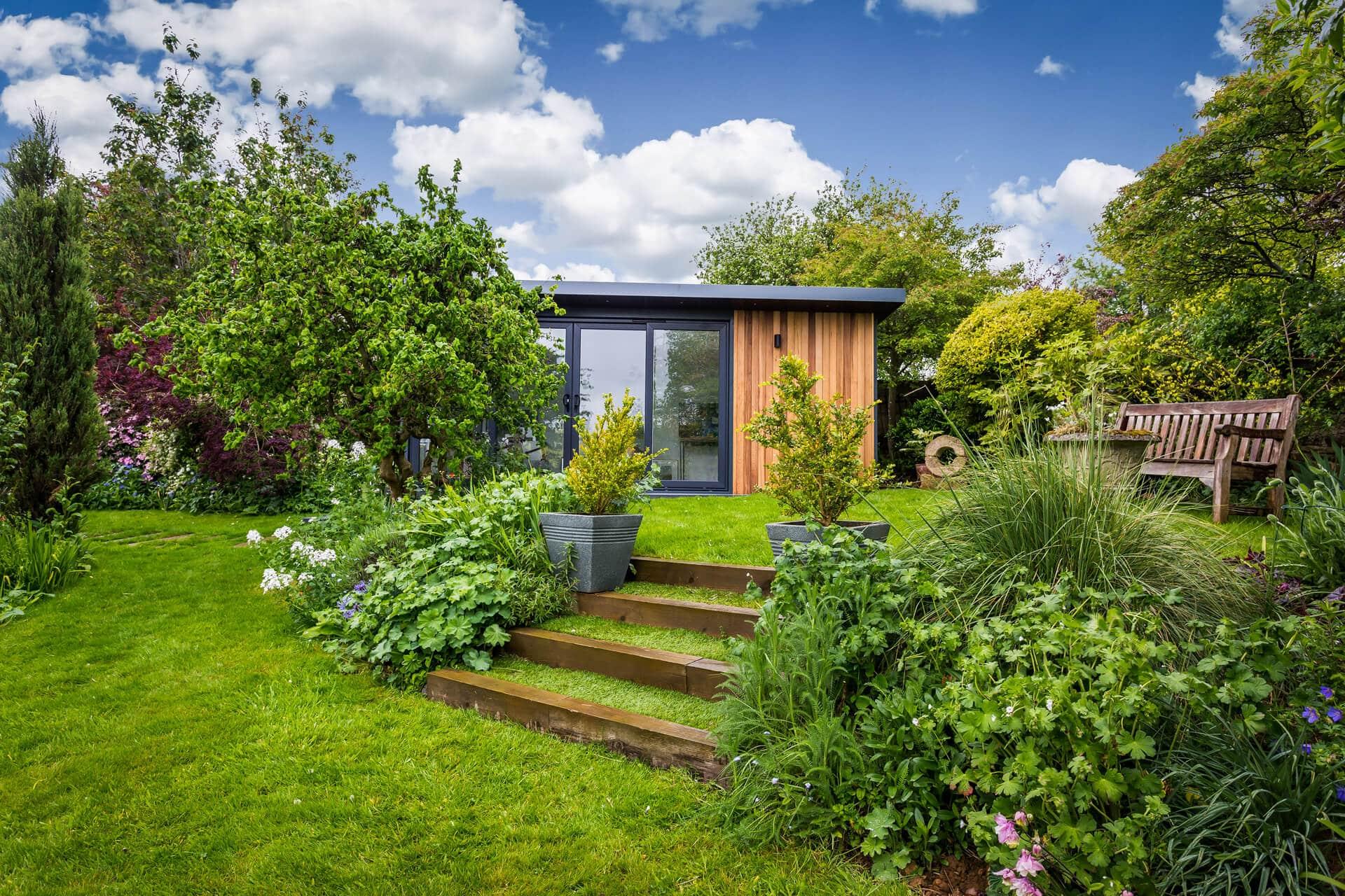 Exterior view of cedar clad garden room located in lush green garden with mature shrubs