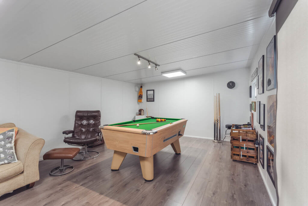 Shot of pool table and comfy chair in inspiration building