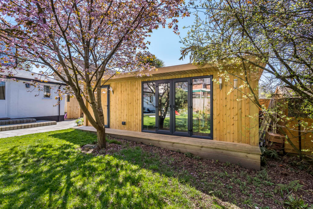Garden room in large garden with french doors clad in scandinavian redwood