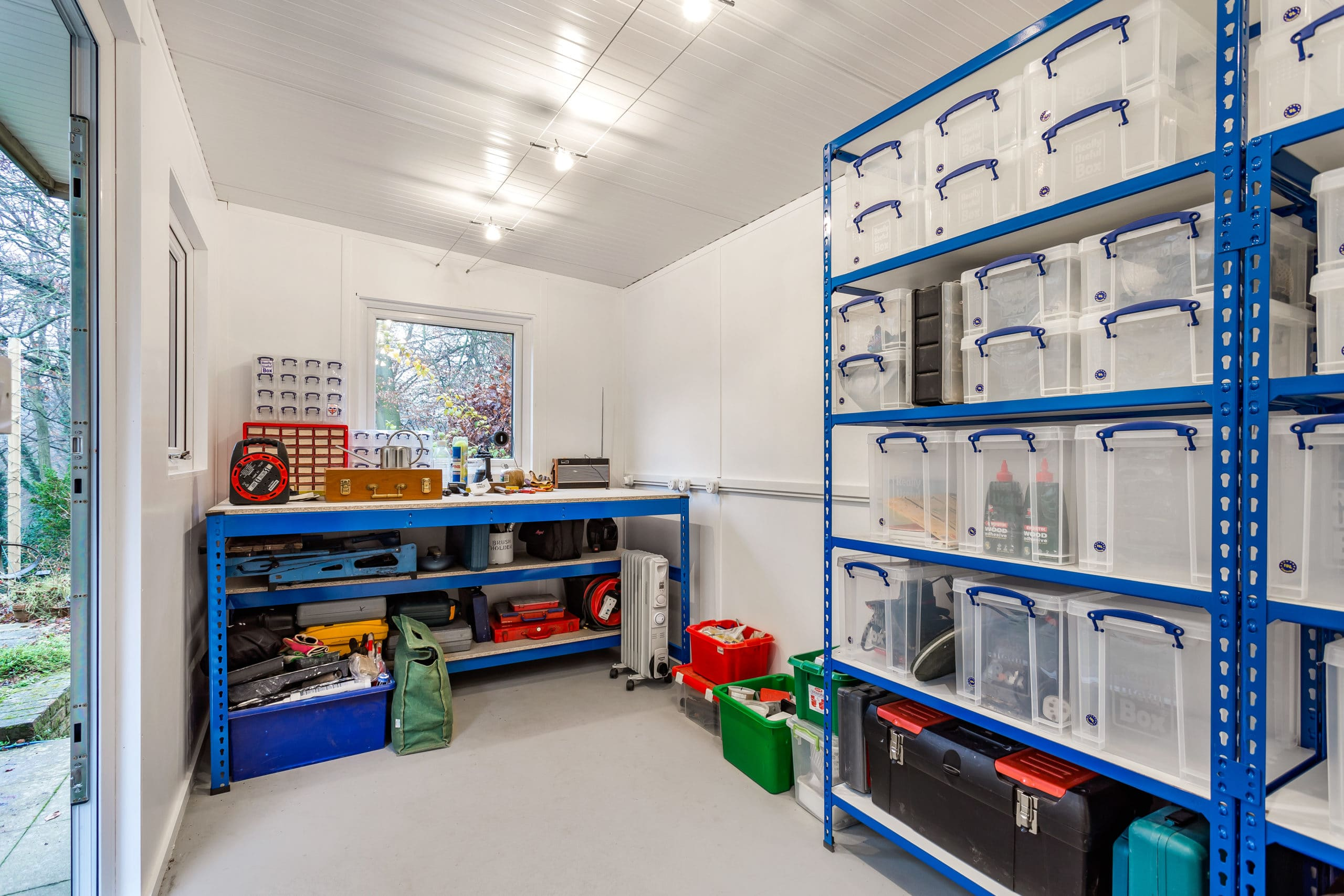 Interior of garden storage workshop with blue metal workbench and clear boxes stacked on shelving