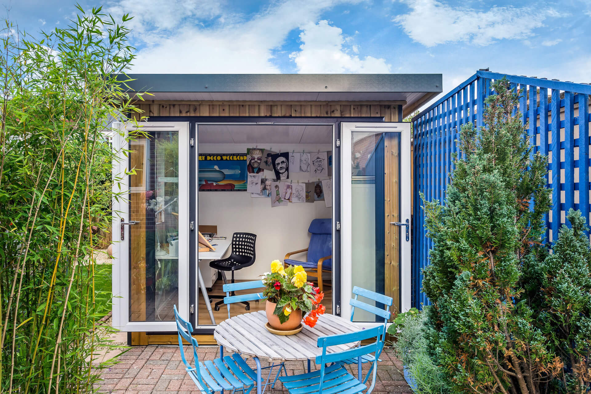 Wooden table and blue metal chairs sit in front of open garden art studio with its french doors open wide.