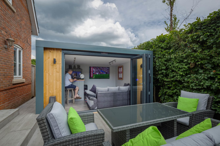 Exterior of Inspiration with bi-folds open looking into man cave with man on bar stool and garden furniture in front of the building