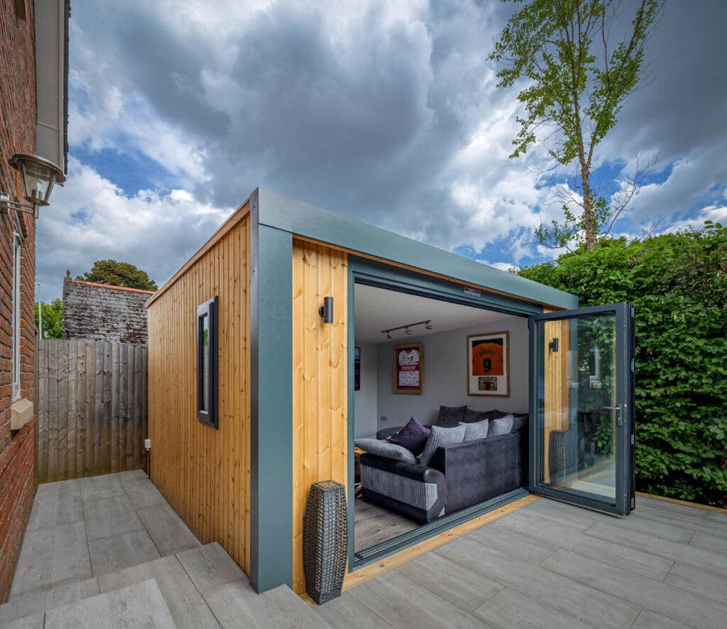 Exterior side angle photo of an Inspiration with bi-folds open looking into man cave with L shaped grey sofa