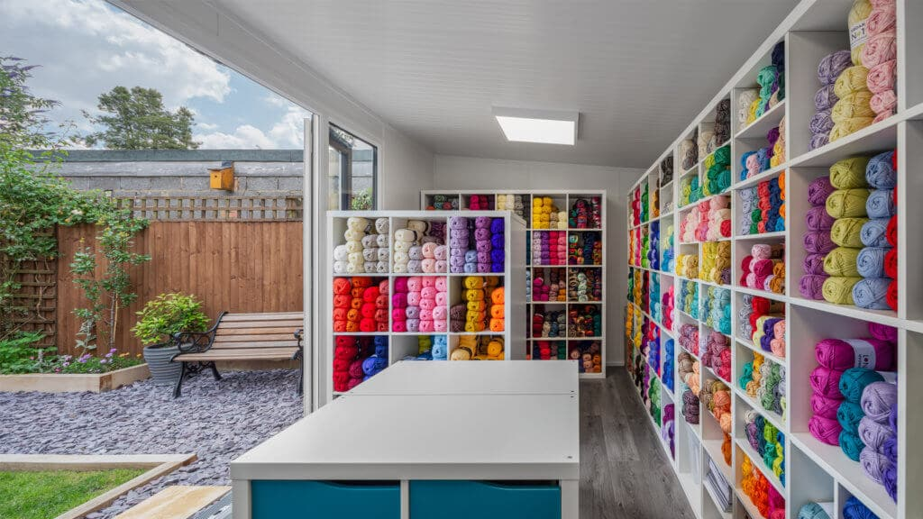 Interior of home office being used as a yarn business with shelves of colourful yarn inside