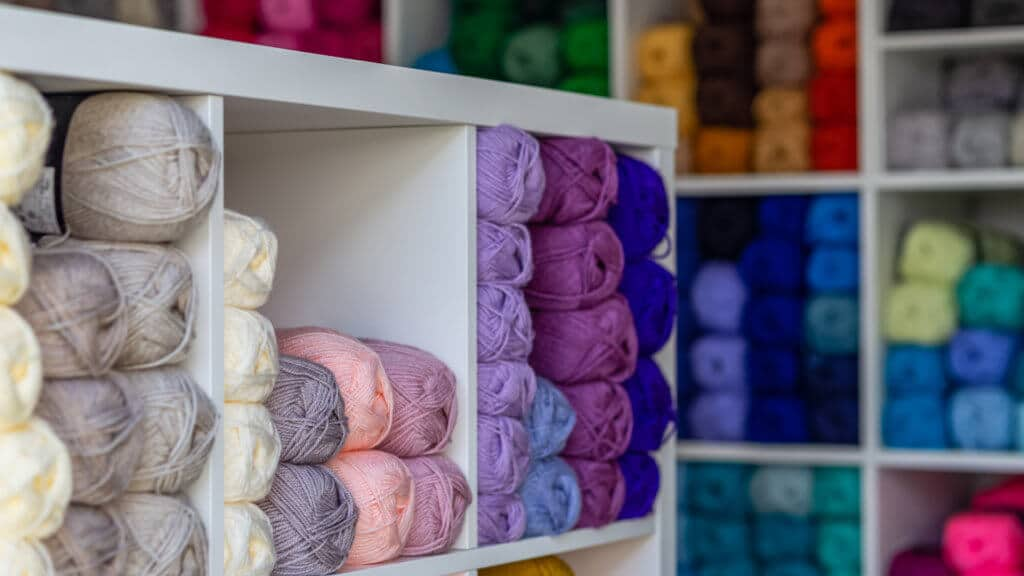 Home office being used as a yarn business with shelves of colourful yarn inside