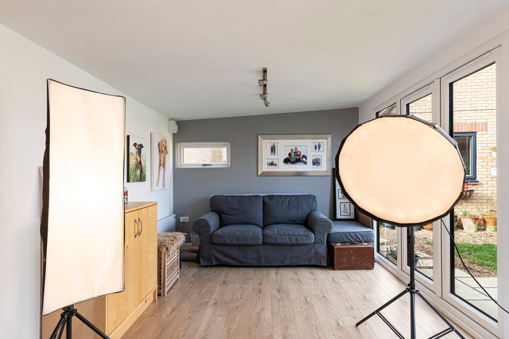 Interior of Inspiration photography studio with spotlights and a grey sofa on the back wall