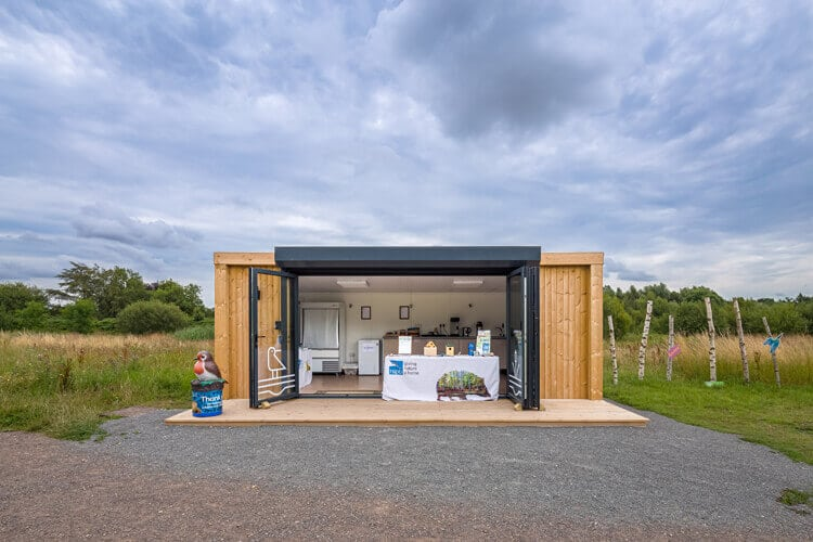 A garden room with doors open in a nature reserve
