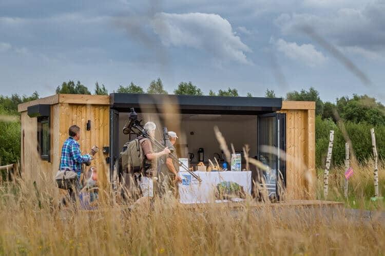A garden room with open doors slightly obstructed with tall grass and photographers walking past