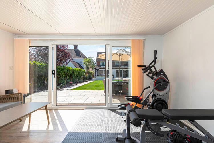 Section of the interior of a garden room with gym equipment