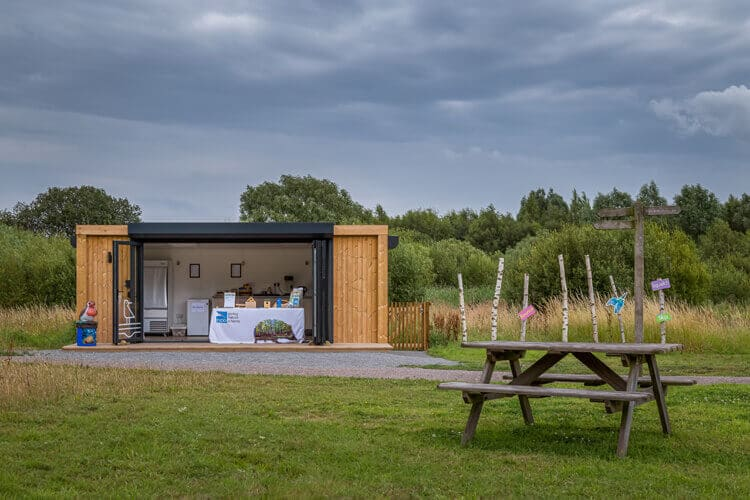 A garden room with doors open in a nature reserve with a picnic table in the foreground