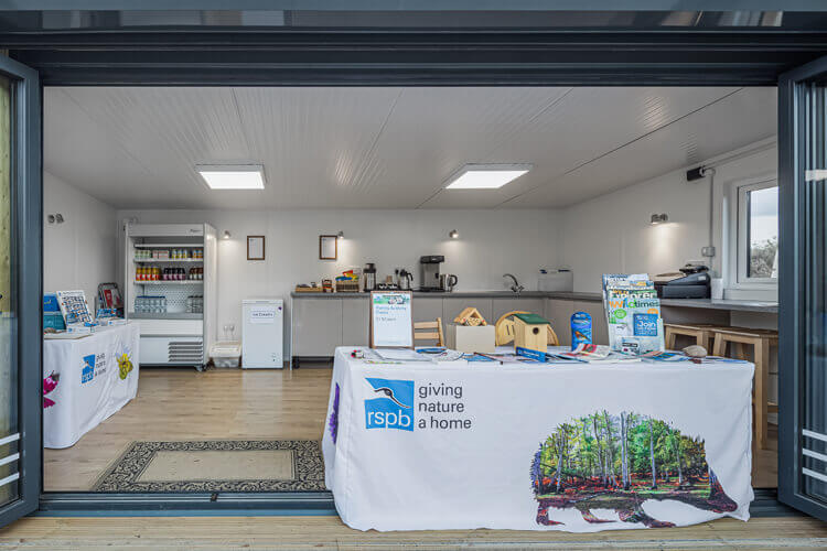Close up of the internal of a garden room with a table showing the RSPB logo