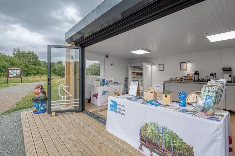 Close up of the internal of a garden room from the side with a table showing the RSPB logo