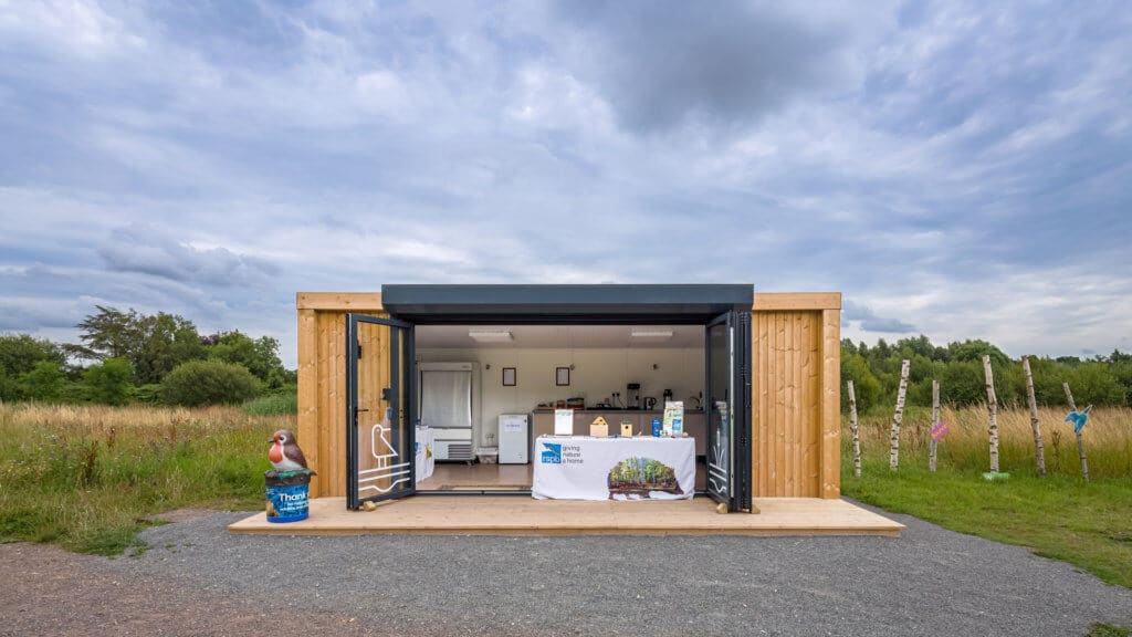 Exterior of an Inspiration used as RSPB welcome hub with a table with flyers on it