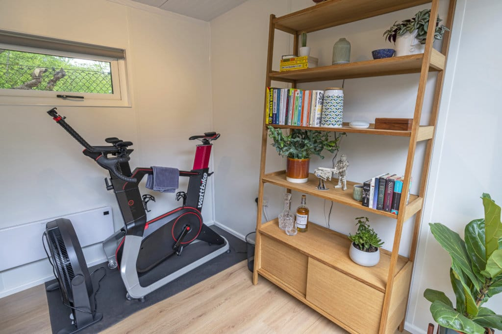 Interior of a garden office with an exercise bike and book shelf