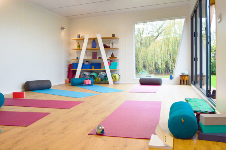 Interior of Pinnacle garden room used as a yoga studio with colourful yoga mats on the floor