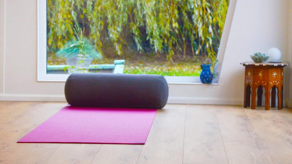 Interior of Pinnacle garden room used as a yoga studio with a pink yoga mat on the floor and a small table in the corner