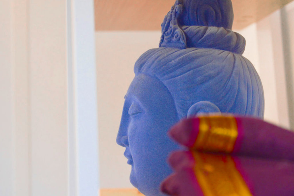 A buddha head with some fabric to the side