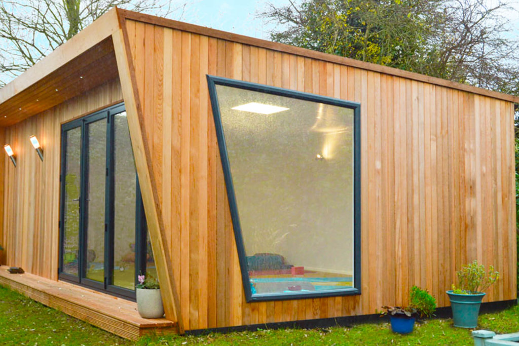 Exterior of Pinnacle garden room used as a yoga studio with a pink yoga mat on the floor and a small table in the corner
