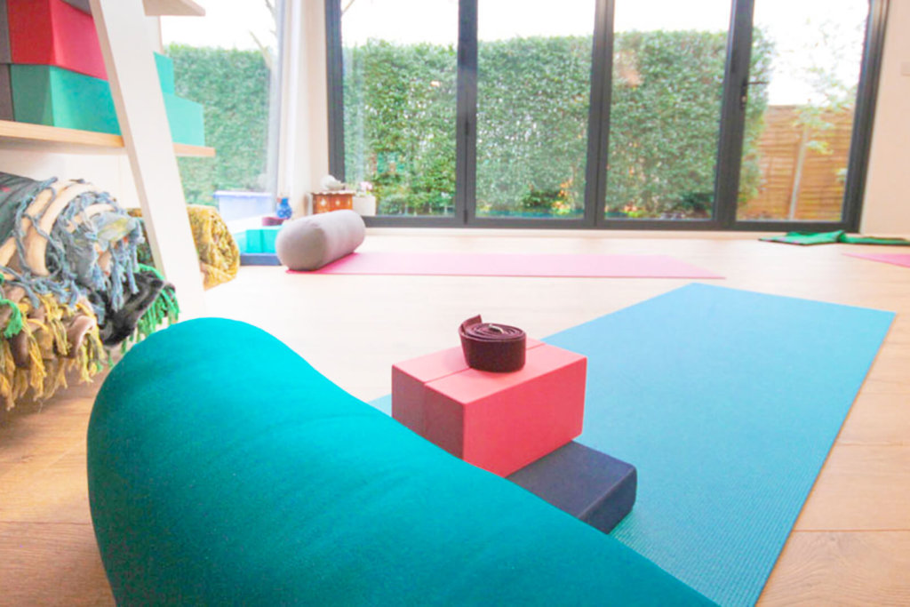 Interior of Pinnacle garden room used as a yoga studio with a pink yoga mat on the floor