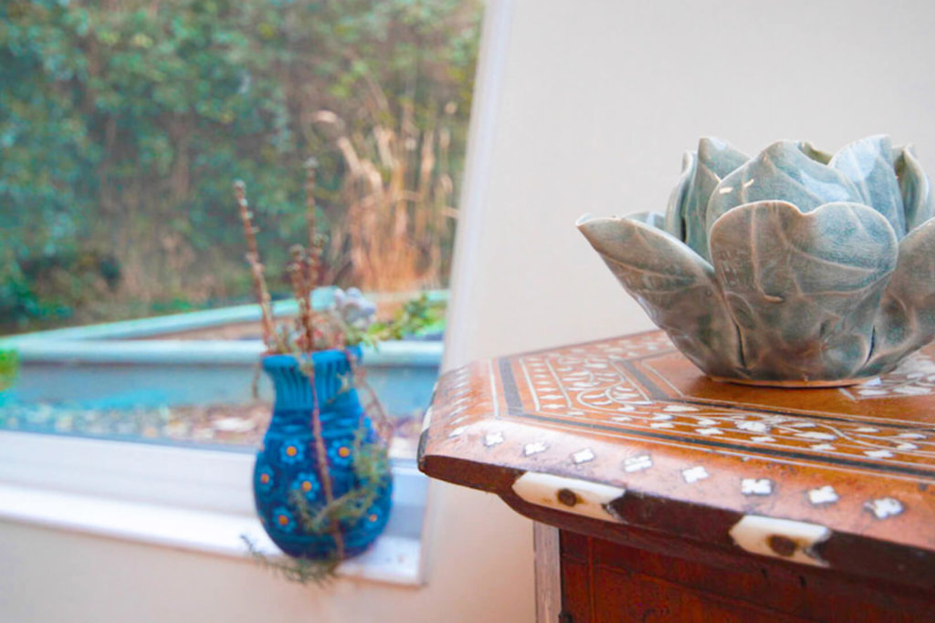 Corner of a Pinnacle yoga studio with a small wooden table and vase