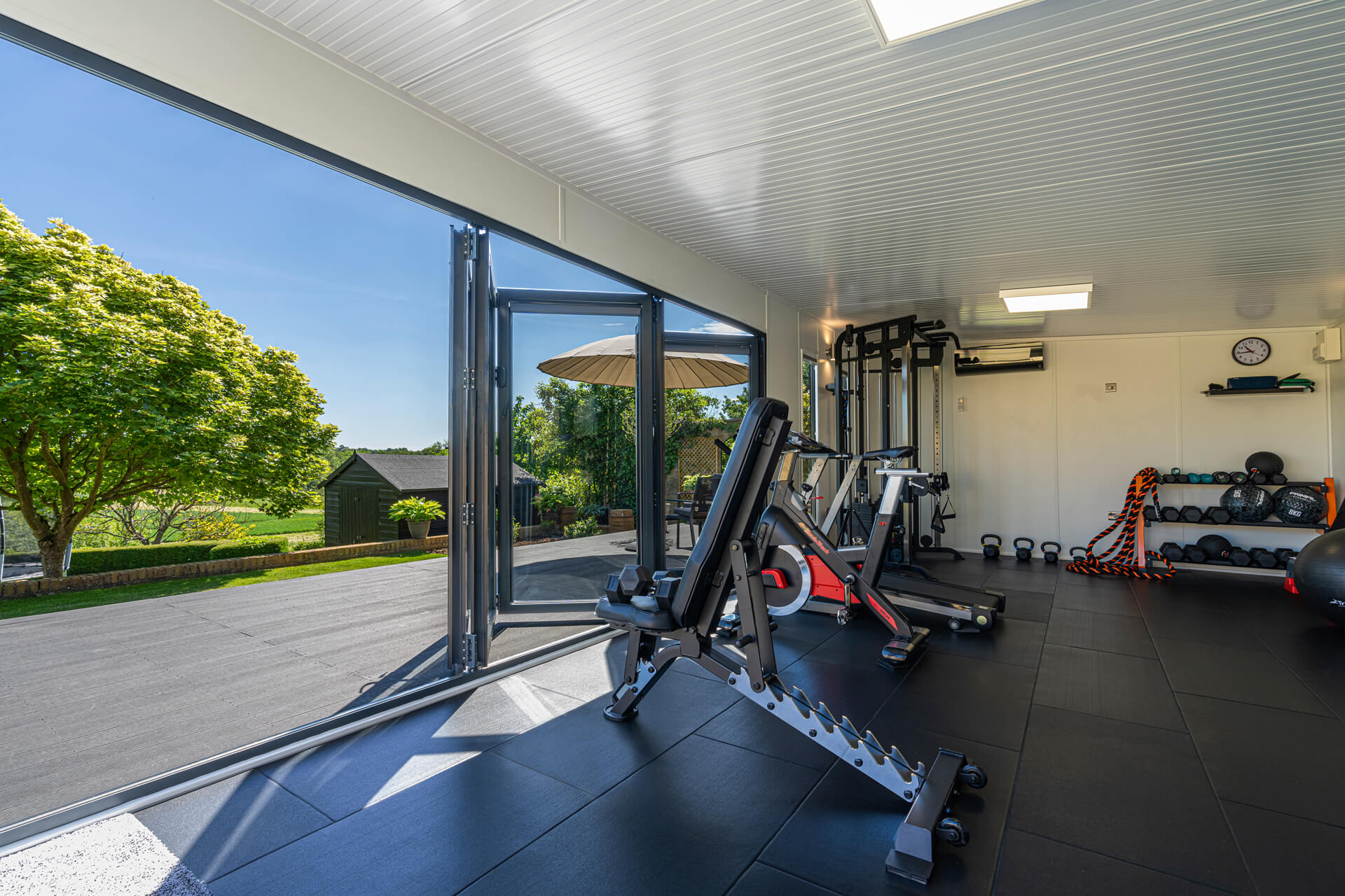 Home gym with bifold doors open on decking and garden beyond a beautiful sunny day.