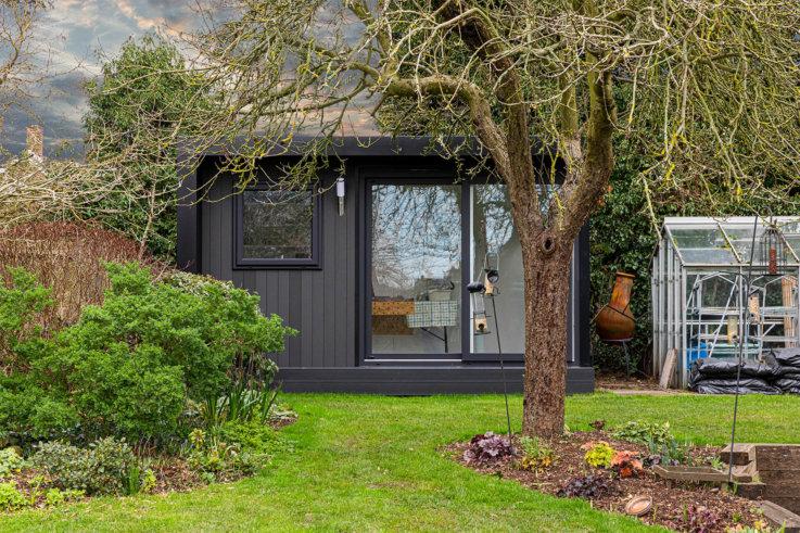 Garden room clad in black composite with sliding door to enter home art studio