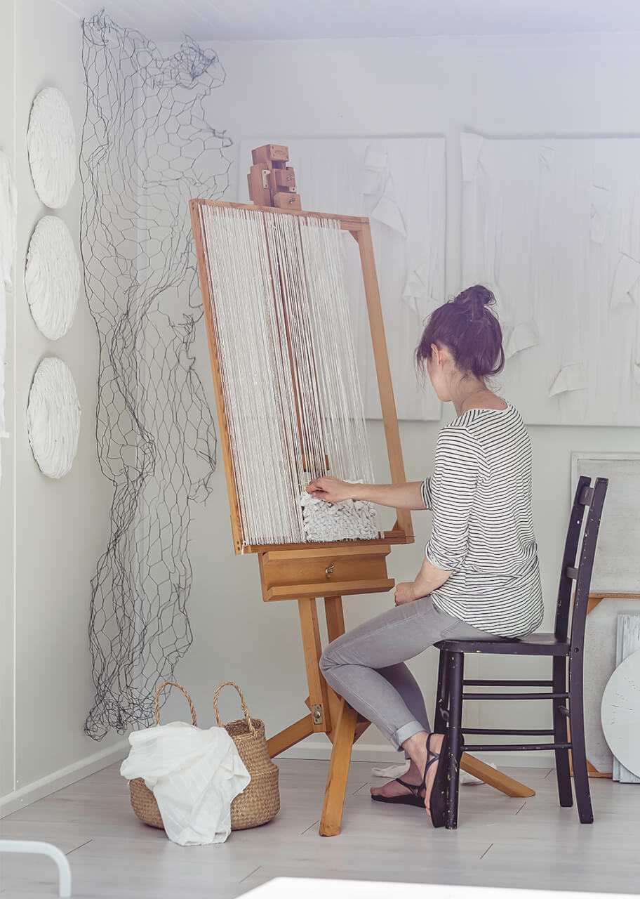 Multimedia artist working at an easel
