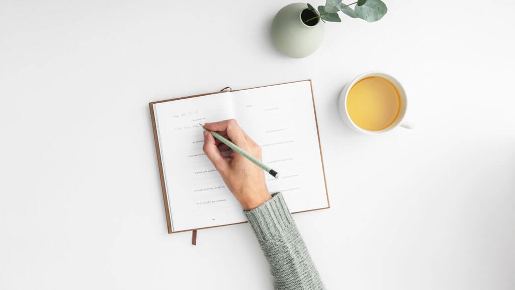 Person writing in a planner with a cup of tea to the right