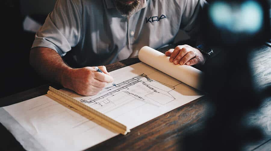 man writing down building plans