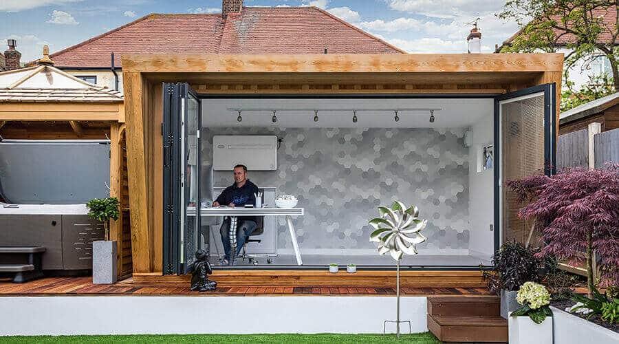 man working in garden room office