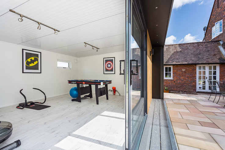 Joint interior and exterior view of garden games room with light oak flooring and pool table