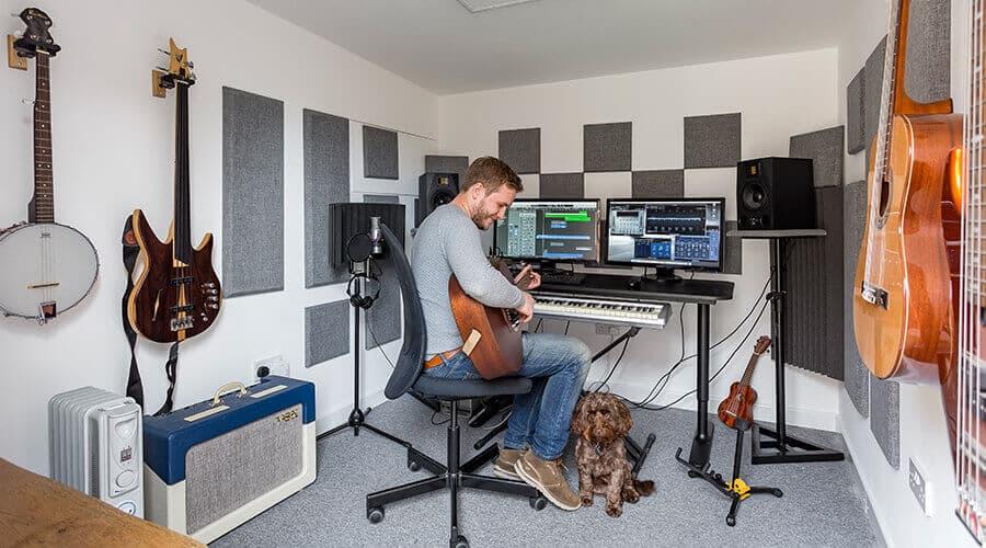 man playing guitar with dog