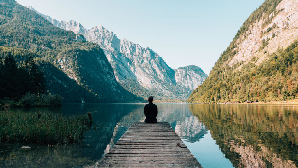 Mountain range with lake and man sitting meditating