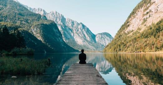 Mountain range with lake and man sitting meditating