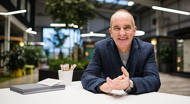 Architectural guru and presenter Kevin McCloud sat at table smiling directly at the camera. Green showroom blurred in background.