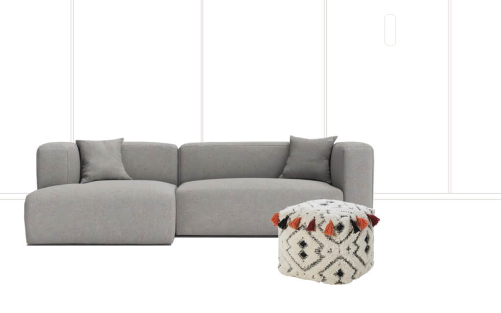 room with grey sofa and pouffe with tassels