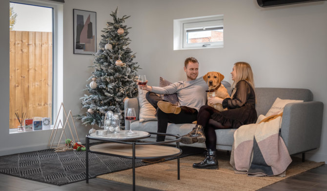 Interior of Annex at Christmas with man and woman on sofa with a Labrador